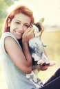 Young girl loving her bunny hugging a red haired with the is sitting and the little animal intense sun behind glamorous glow and Royalty Free Stock Photography