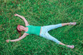 Young girl lying on bright green grass with outstretch Royalty Free Stock Photo