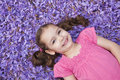 Young girl lying among fallen purple flowers Stock Photography