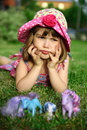 Young girl lying on grass, holding head in hands Stock Photos