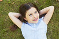 Young girl lying on grass smiling looking away Stock Images