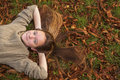 Young girl lying on the ground with fallen leaves in autumn park pretty Royalty Free Stock Photos
