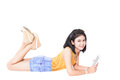 Young girl lying and smile using tablet pc happy working on touching screen model is a asian woman Royalty Free Stock Photo