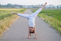Young girl makes a cartwheel on a path Royalty Free Stock Photo