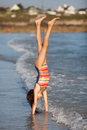 Young girl makes a handstand at the seafront Royalty Free Stock Photo