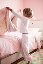 Young girl making her bed by herself at home Stock Photos