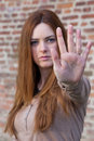 Young girl making stop gesture with focus on the hand redhead over red brick walll background Royalty Free Stock Image