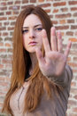 Young girl making stop gesture with her hand selective focus redhead on the face over red brick wall background Stock Photo