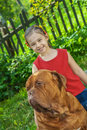 Young girl and mastiff smiling astride big dog of breed french dogue de bordeaux Royalty Free Stock Images