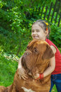 Young girl and mastiff smiling astride big dog of breed french dogue de bordeaux Stock Image