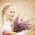 Young Girl Outdoors. Happy Girl with Heather Flowers Royalty Free Stock Photo