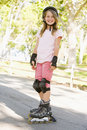 Young girl outdoors on inline skates smiling Royalty Free Stock Image