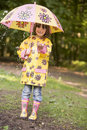 Young girl outdoors in rain with umbrella smiling Stock Images