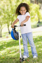 Young girl outdoors on scooter smiling Stock Photo