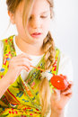 Young girl painting an easter egg red Stock Images