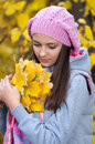 Young girl in a park in autumn with yellow leaves Stock Images
