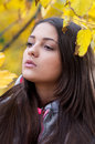 Young girl in a park in autumn with yellow leaves Royalty Free Stock Photos