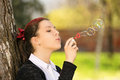 Young girl in a park making soap bubbles Royalty Free Stock Photo