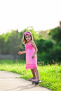 Young girl in pink dress riding on skateboard Royalty Free Stock Photography