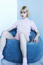 A young girl in a pink home suit near a soft chair. Beautiful model poses for fashion magazine. Picture in calm gray-blue tones Royalty Free Stock Photo
