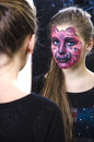 Young girl pink panther makeup looks mirror Stock Image