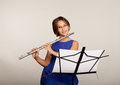 Young girl playing a flute in blue dress Stock Images
