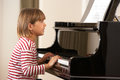 Young girl playing grand piano Royalty Free Stock Photography
