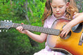 Young girl playing guitar Stock Photos