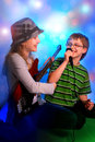 Young girl playing guitar and boy singing the bass with microphone on stage Royalty Free Stock Photos