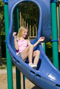 Young girl playing on a slide at the park Royalty Free Stock Photography
