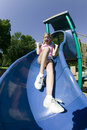 Young girl playing on a slide at the park Stock Photos