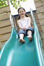 Young girl playing on slide in park full length of pretty Royalty Free Stock Photos