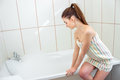 A young girl with a ponytail and a towel on the body sits on the bathtub and tries to hand water Royalty Free Stock Photo
