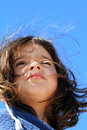 Young girl portrait hairy at the beach under a clean blue sky background Royalty Free Stock Photo