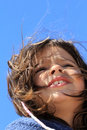 Young girl portrait windy day over clean blue background Royalty Free Stock Photos