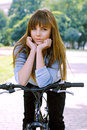 Young girl posing on a bicycle in the park Stock Photos