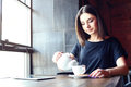Young girl pouring tea in coffee shop portrait of attractive while sitting alone during free time lifestyle Royalty Free Stock Photos