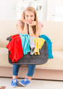 Young girl preparing her luggage suitcase before travel she is in doubt of what to pack Stock Photos