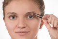 Young girl pulls out her eyebrows with tweezers metal on a white Royalty Free Stock Photo