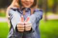 Young girl puts her big thumbs up portrait of cheerful kid smiling having fun outside happy successful person Stock Photos
