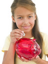Young girl putting coin into piggy bank Stock Images