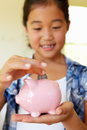 Young girl putting money in piggybank Royalty Free Stock Photo