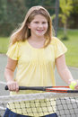 Young girl with racket on tennis court smiling Royalty Free Stock Photo