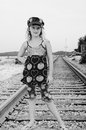 Young girl on a railroad tracks posing with the maine coast in the background wearing hat and heart outfit Royalty Free Stock Photos
