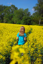 Young girl in rape field Stock Image