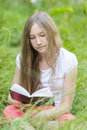 Young girl reading book on field vertical photo Royalty Free Stock Photo