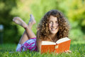 Young girl reading book while lying on grass teenage red Stock Photos
