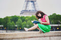 Young girl reading a book near the Eiffel tower Royalty Free Stock Photo