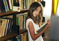 Young girl reading a book from shelf in library. Stock Images