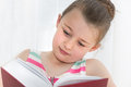 Young girl reading a a large hard back book Stock Photos